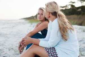 twee zussen zitten op het strand bij zonsondergang