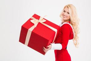 Cheerful female in santa claus clothes holding big red present