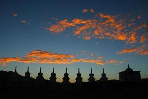 Sunset glow and silhouettes of white stupas on Tibetan Plateau