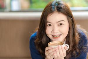 Happy asian smiling female student drinking coffee