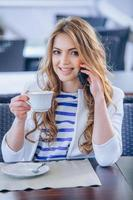 Young woman at cafe drinks coffee and talking on the