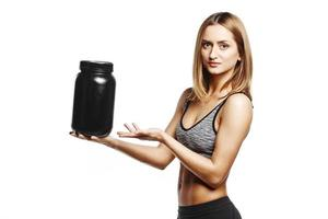 pretty fitness girl holding jar of sports nutrition photo