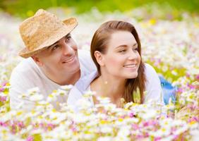 Beautiful couple on chamomile meadow