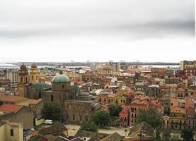 horizonte de cagliari con edificios, puerto, mar gris nubes sombrías foto