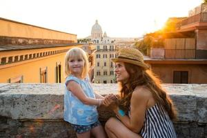 mãe ajoelhada pela filha acima de Roma ao pôr do sol