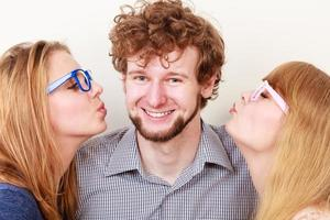 Two pretty young women kissing handsome man.