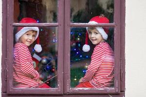 Two cute boys, brothers, looking through window, waiting Santa