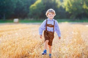 Funny little kid boy in leather shorts walking wheat field photo