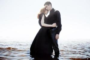 beautiful young couple hugging standing in the sea, photo colorization