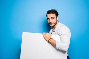 handsome man with beard casual dressed holding a blank panel