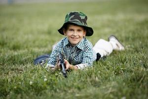 little boy with airgun outdoors photo