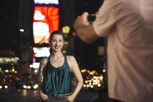 hombre fotografiando mujer en Times Square en la noche