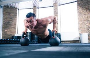 uomo muscoloso che fa push up in palestra