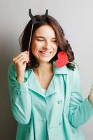 Funny woman with horns holding a heart. photo