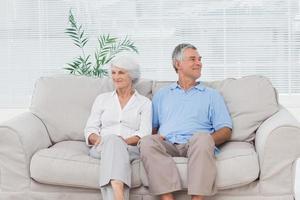 Elderly couple sitting on sofa photo