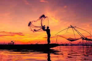 Throwing fishing net during sunset photo