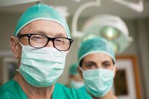 cirujano sonriente cruzando sus brazos con un colega foto