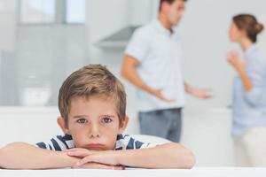 niño triste con los brazos cruzados mientras los padres peleaban foto