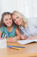 Madre ayudando a la hija con la tarea en la sala de estar foto