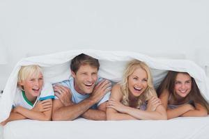 padres acostados en la cama con sus hijos foto