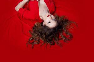 vrouw in jurk ligt op een rode achtergrond