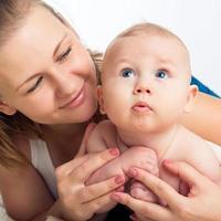 Retrato de la hermosa joven madre sonriente con un bebé.