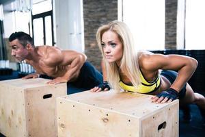 mujer y hombre haciendo flexiones en el gimnasio