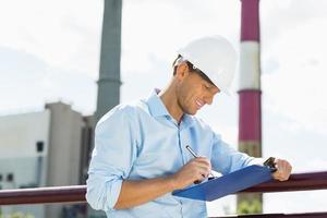 Arquitecto hombre escribiendo en el portapapeles en el sitio foto