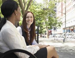 dos colegas mujeres hablando en la calle foto