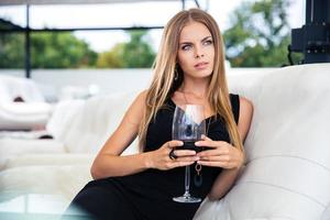 Thoughtful woman with glass of wine photo