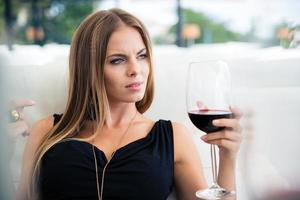 Woman sitting in restaurant with glass of wine photo