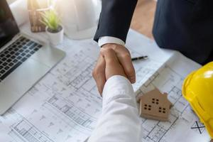 Two business professionals shake hands over blueprint