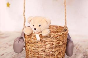 Teddy bear toy sitting in the balloon basket