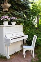 White piano and chairs in summer garden