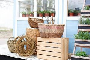 Wicker baskets sit on the porch a blue country house