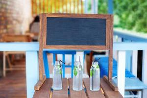 A blank chalkboard sits above glasses of lemonade