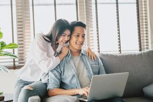 Asian couple using laptop on sofa at home photo
