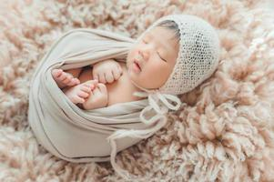 Newborn baby wrapprd in cocoon sleeping on fur