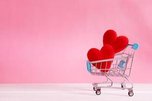 Red heart shapes in shopping cart on pink background