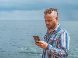 Bearded man with a mohawk holds a phone in his hand