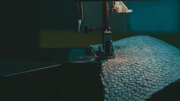 A sewing machine sews burlap fabric