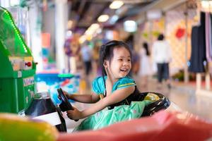 Little Asian girl rides on toy car in mall