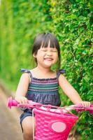Happy little girl rides a bicycle in the park