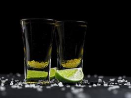 Two shots of tequila gold with lime