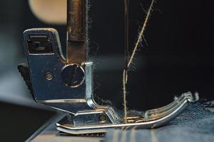 A sewing machine sews denim
