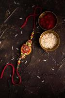 Rakhi, rice grains and kumkum on textured dark background