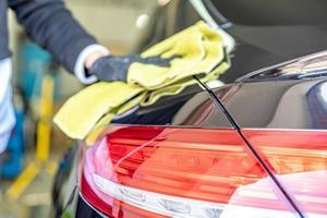 Mechanic polishing car body in the garage