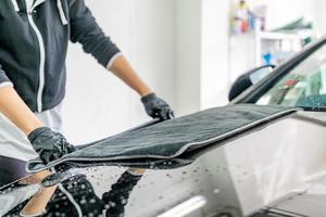 Mechanic drying off hood of car