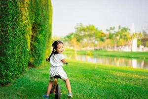 Young girl rides balance bike in the park