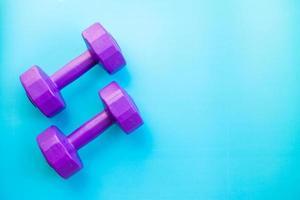 pesas de color púrpura sobre fondo azul foto